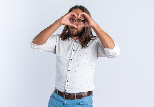 흰 벽에 격리된 눈 앞에서 사랑의 사인을 하는 카메라를 바라보는 안경을 쓴 자신감 있는 성인 미남