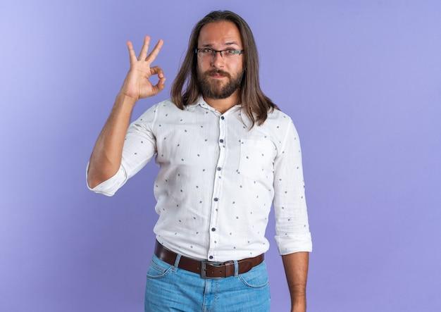 Fiducioso bell'uomo adulto con gli occhiali che guarda la telecamera facendo segno ok isolato sul muro viola con spazio copia