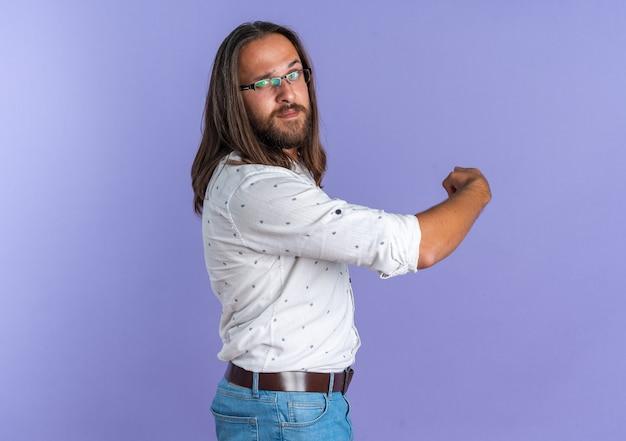 コピースペースと紫色の壁に隔離された後ろを指しているカメラを見て縦断ビューで立っている眼鏡をかけている自信を持って大人のハンサムな男