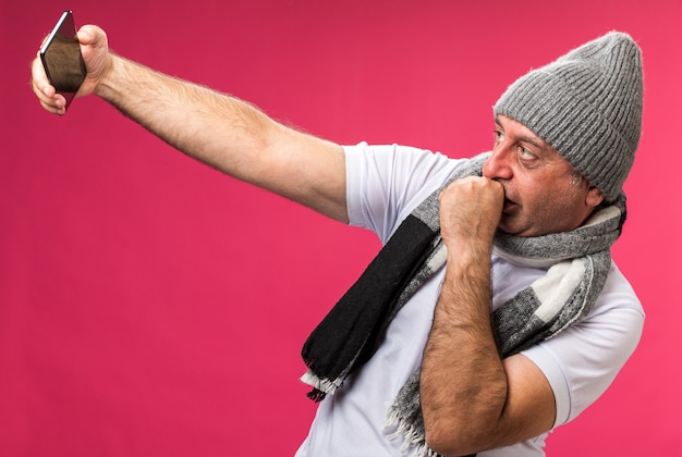 Confident adult ill caucasian man with scarf around neck wearing winter hat looking at phone taking selfie and keeping fist close to mouth isolated on pink wall with copy space