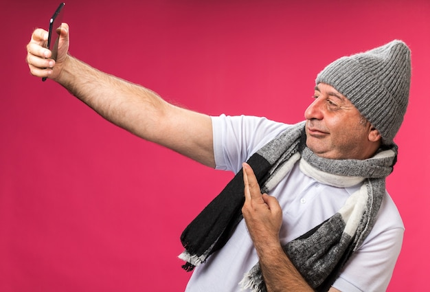 Confident adult ill caucasian man with scarf around neck wearing winter hat taking selfie gesturing victory sign isolated on pink wall with copy space Free Photo