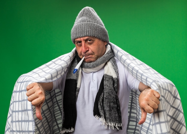 Confident adult ill caucasian man with scarf around neck wearing winter hat wrapped in plaid thumbs down holding thermometer in his mouth isolated on green wall with copy space