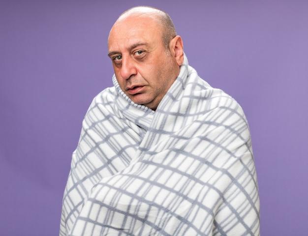Fiducioso adulto malato uomo caucasico avvolto in plaid isolato sulla parete viola con spazio di copia