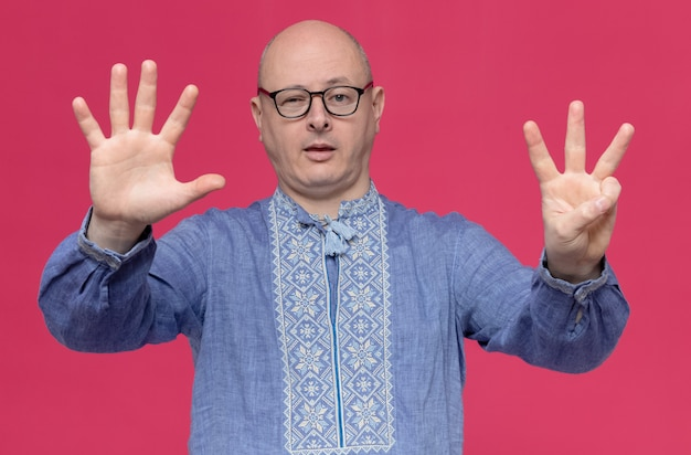Confident adult man in blue shirt wearing glasses gesturing eight with fingers