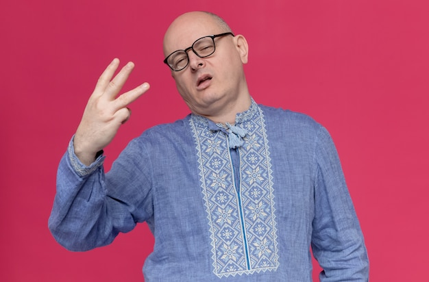 Confident adult man in blue shirt wearing glasses gesturing three with fingers