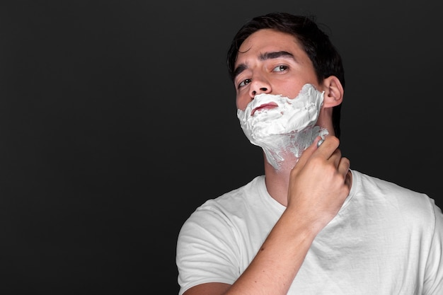 Confident adult man shaving his beard