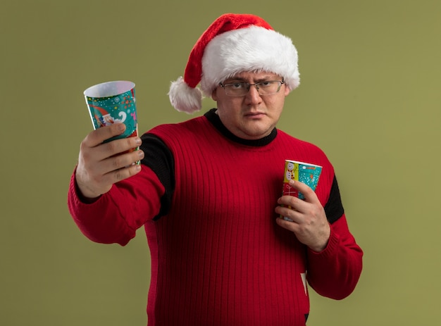 眼鏡とサンタの帽子をかぶって、オリーブグリーンの壁に隔離されたそれらの1つを伸ばしてクリスマスコーヒーカップを保持している自信のある大人の男