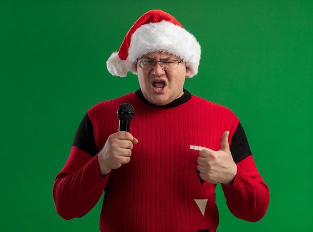 안경과 산타 모자를 쓰고 자신감이 성인 남자는 녹색 배경에 고립 엄지 손가락을 보여주는 카메라를보고 마이크를 들고