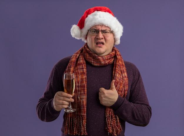 紫色の壁に分離された親指を示すシャンパンのガラスを保持している首の周りにスカーフとメガネとサンタ帽子を身に着けている自信を持って大人の男