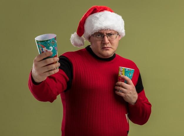 Fiducioso uomo adulto con gli occhiali e il cappello di babbo natale che tengono tazze di caffè di natale che allungano uno di loro fuori isolato sul muro verde oliva