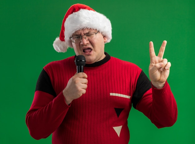 Confident adult man wearing glasses and santa hat talking into microphone looking at camera doing peace sign isolated on green background