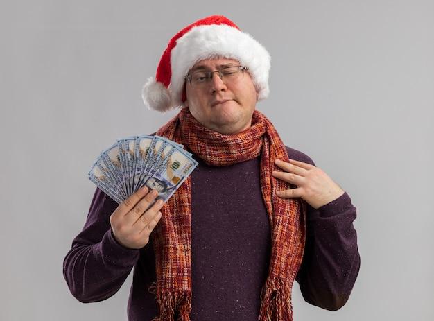 Fiducioso uomo adulto che indossa occhiali e cappello da babbo natale con sciarpa intorno al collo che tiene soldi mordendosi il labbro toccando la spalla isolata sul muro bianco