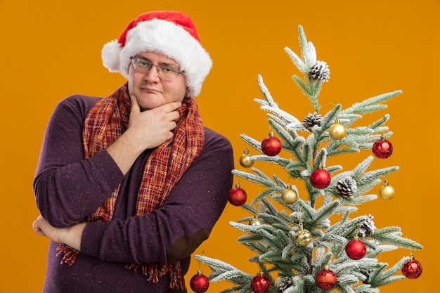 Fiducioso uomo adulto con gli occhiali e cappello da babbo natale con sciarpa intorno al collo in piedi vicino all'albero di natale decorato tenendo la mano sul mento isolato sul muro arancione