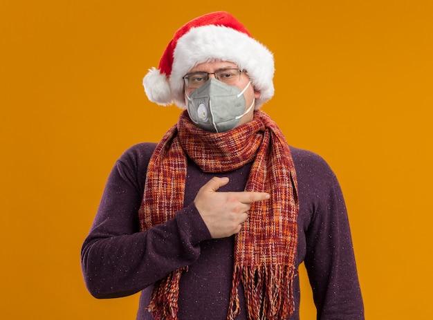 Fiducioso uomo adulto che indossa occhiali maschera protettiva e cappello santa con sciarpa intorno al collo guardando la telecamera rivolta verso il lato isolato su sfondo arancione