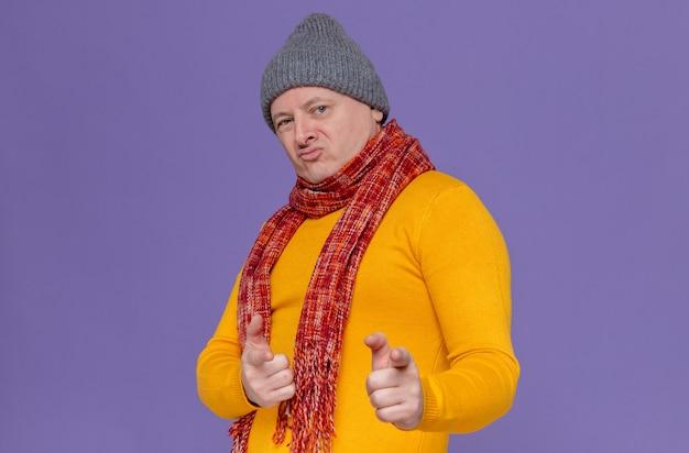 冬の帽子と首の周りにスカーフを見て、正面を指して自信を持って大人の男