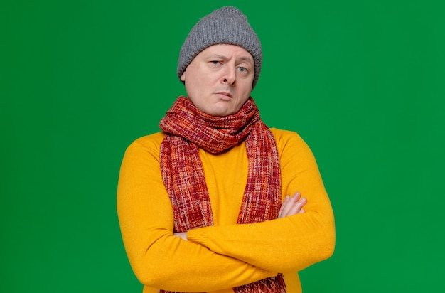 Confident adult man with winter hat and scarf around his neck standing with crossed arms and looking