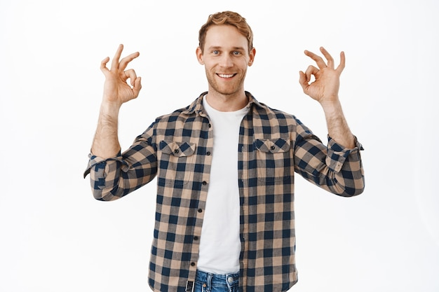 Confident adult redhead man showing yes ok okay gesture and smiling happy, guarantee everything under control, no problem, alright gesture, nod in approval, praise good quality, white wall