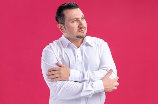 Fiducioso uomo d'affari slavo adulto in piedi con le braccia incrociate e guardando a lato