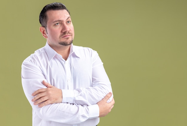 Confident adult slavic businessman standing with crossed arms and looking at side