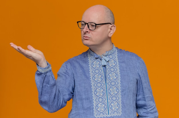 Confident adult slavic man in blue shirt and with glasses looking and pointing at side with his hand