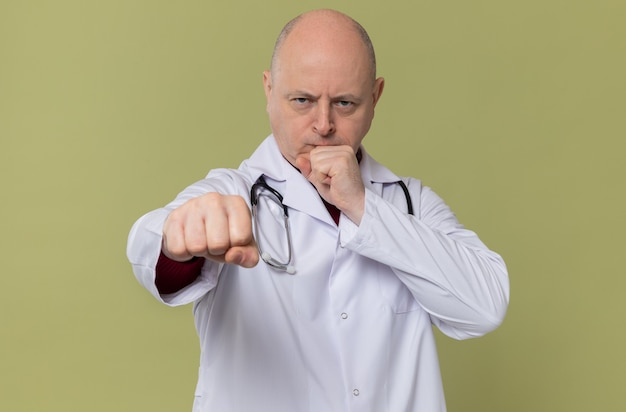Confident adult slavic man in doctor uniform with stethoscope clenching his fists and looking at front