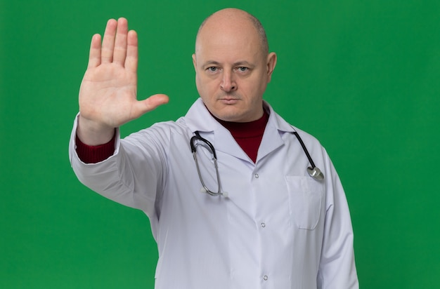 Confident adult slavic man in doctor uniform with stethoscope gesturing stop hand sign