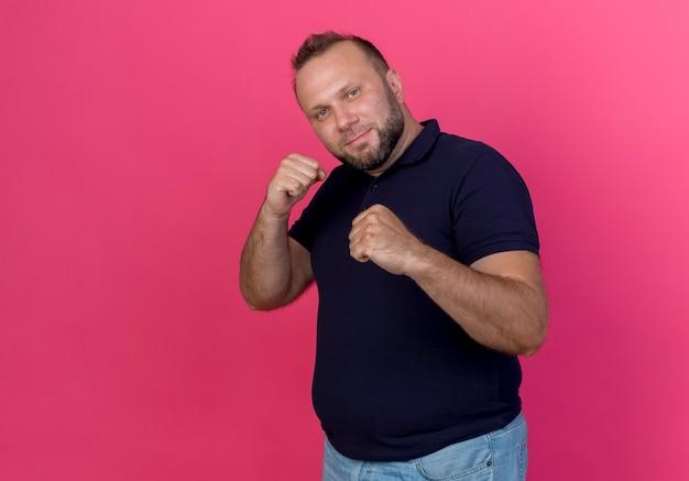 Uomo slavo adulto sicuro che fa gesto di boxe isolato