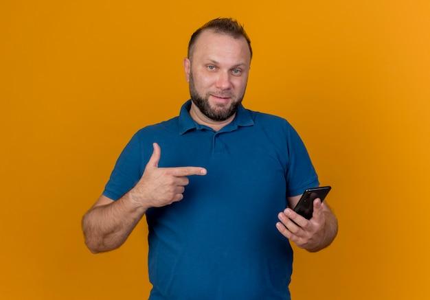 自信を持って大人のスラブ人が携帯電話を持って指さしている