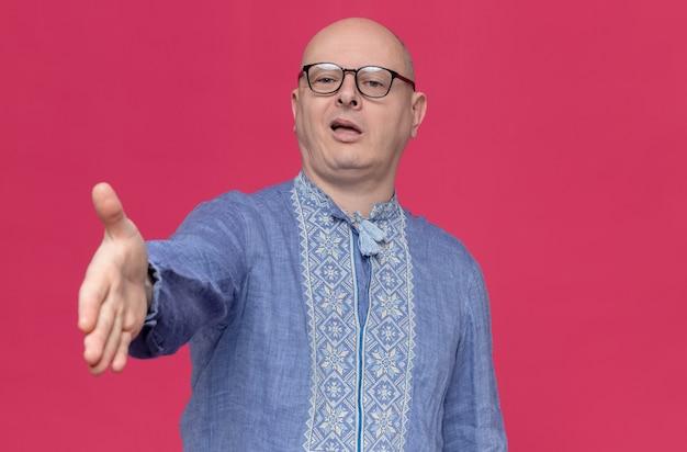 Уверенный взрослый славянский мужчина в синей рубашке в оптических очках, протягивая руку