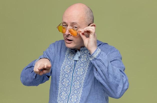 카메라를 보고 가리키는 선글라스를 끼고 파란색 셔츠를 입은 자신감 있는 성인 슬라브 남자