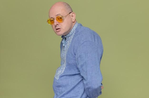 옆으로 서서 선글라스를 끼고 파란색 셔츠를 입은 자신감 있는 성인 슬라브 남자