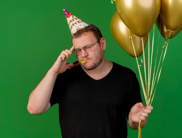 생일 모자를 쓰고 광학 안경에 자신감있는 성인 슬라브 남자가 사원에 손가락을 대고 파티 휘파람을 불고 헬륨 풍선을 들고 있습니다.