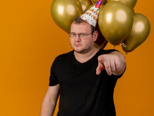 誕生日の帽子をかぶった眼鏡をかけた自信に満ちた大人のスラブ人が、カメラを指すヘリウム風船の前に立つ