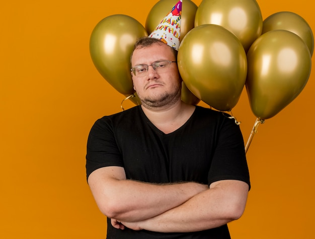 생일 모자를 쓰고 광학 안경에 자신감이있는 성인 슬라브 남자는 헬륨 풍선 앞에서 교차 팔로 서 있습니다.