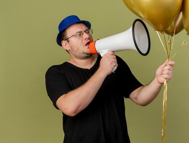 파란색 파티 모자를 쓰고 광학 안경에 자신감있는 성인 슬라브 남자가 들고 시끄러운 스피커로 말하는 헬륨 풍선을 본다.