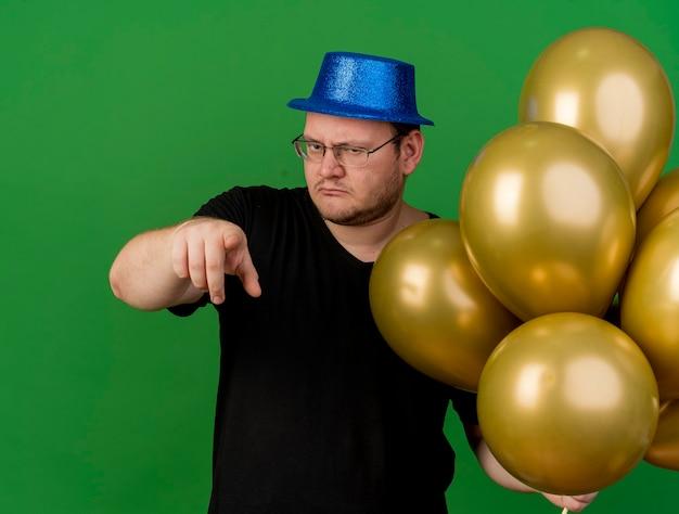 파란색 파티 모자를 쓰고 광학 안경에 자신감이있는 성인 슬라브 남자가 카메라에 헬륨 풍선과 포인트를 보유하고 있습니다.