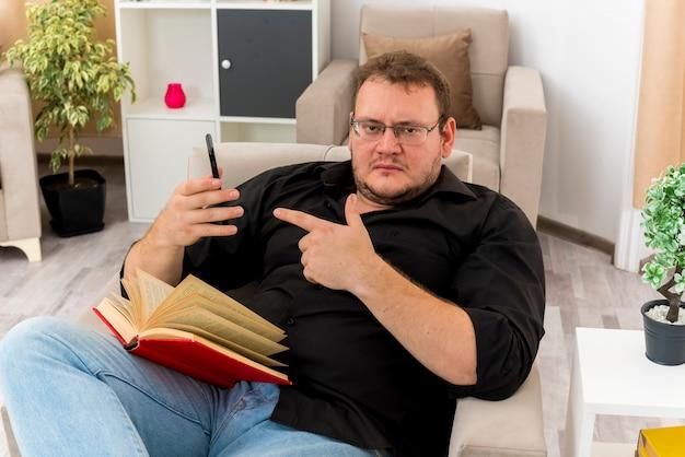 Fiducioso uomo slavo adulto in vetri ottici si siede sulla poltrona tenendo il libro sulle gambe e indicando il telefono all'interno del soggiorno