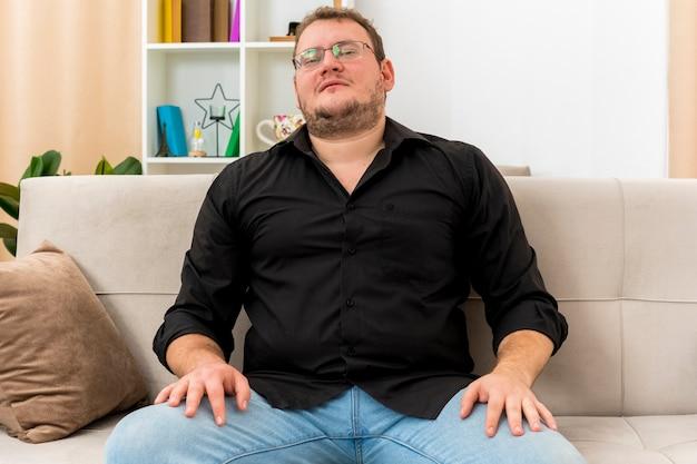 Fiducioso uomo adulto slavo in vetri ottici si siede sulla poltrona mettendo le mani sulle gambe all'interno del soggiorno