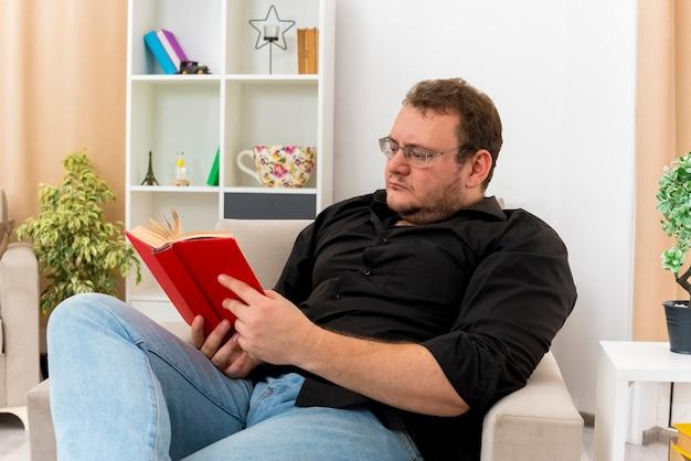 Fiducioso uomo adulto slavo in vetri ottici si siede sulla poltrona leggendo il libro all'interno del soggiorno