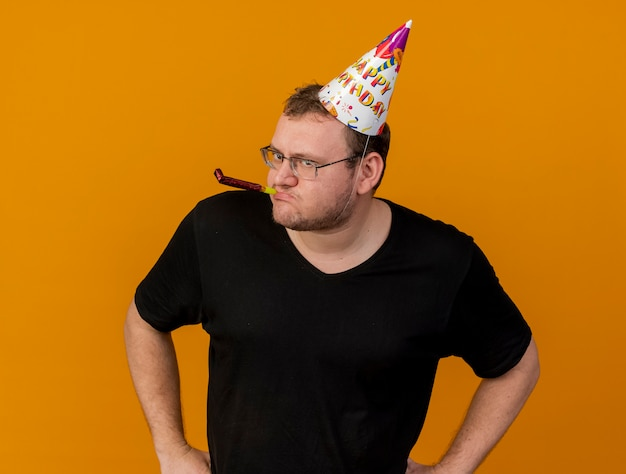 Confident adult slavic man in optical glasses wearing birthday cap blowing party whistle