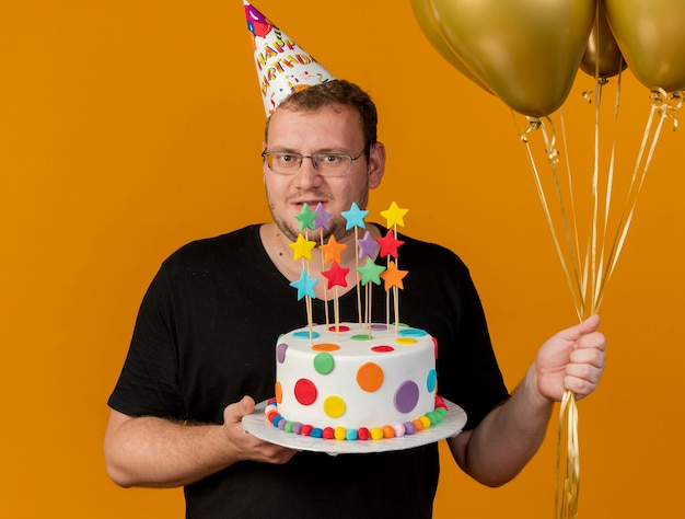 Confident adult slavic man in optical glasses wearing birthday cap holds helium balloons and birthday cake