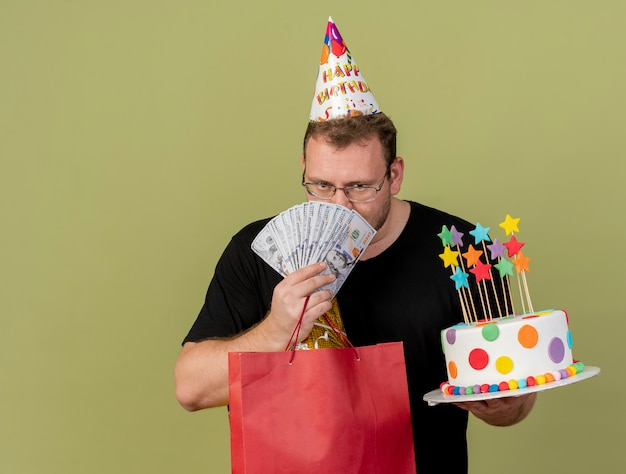 Confident adult slavic man in optical glasses wearing birthday cap holds money paper shopping bag and birthday cake