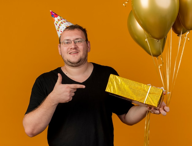 Confident adult slavic man in optical glasses wearing birthday cap holds and points at helium balloons and gift box