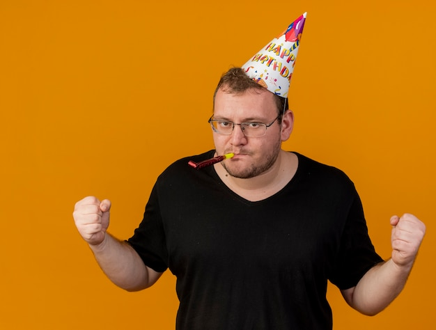 Confident adult slavic man in optical glasses wearing birthday cap keeps fists and blows party whistle