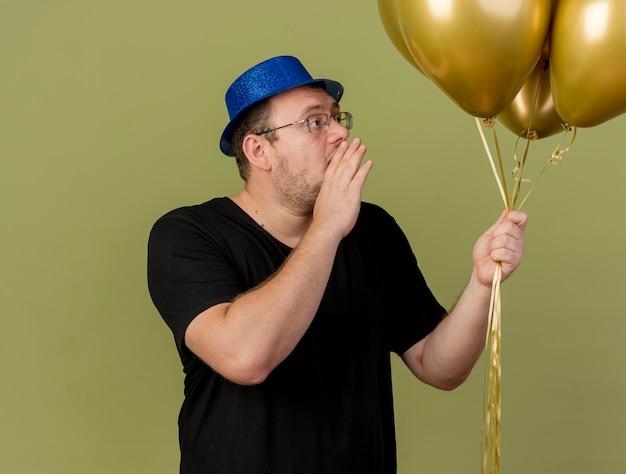 Fiducioso uomo slavo adulto in occhiali ottici che indossa un cappello da festa blu tiene la mano vicino alla bocca guardando palloncini di elio