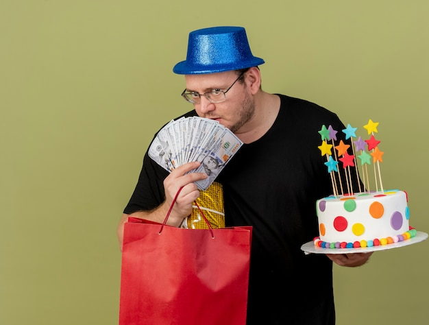 Confident adult slavic man in optical glasses wearing blue party hat holds money gift box paper shopping bag and birthday cake