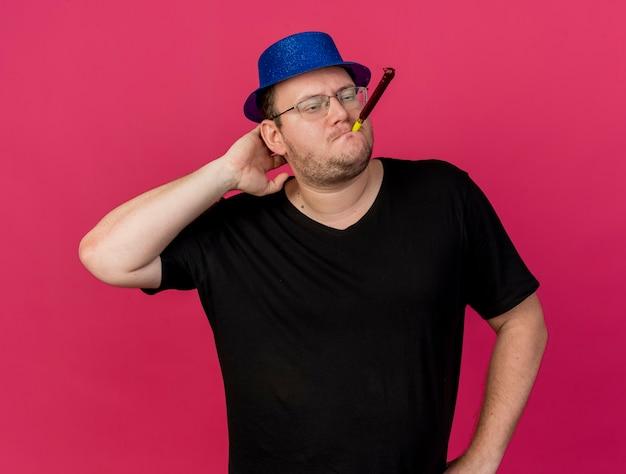 Fiducioso uomo slavo adulto in occhiali ottici che indossa un cappello da festa blu mette la mano sulla testa dietro il fischio del partito di soffiaggio