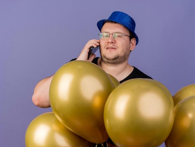 Fiducioso uomo slavo adulto in occhiali ottici che indossa cappello da festa blu sta con palloncini di elio che parla al telefono