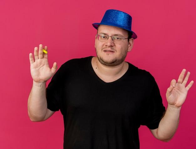Fiducioso uomo slavo adulto in occhiali ottici che indossa cappello da festa blu sta con le mani alzate che tengono il fischietto