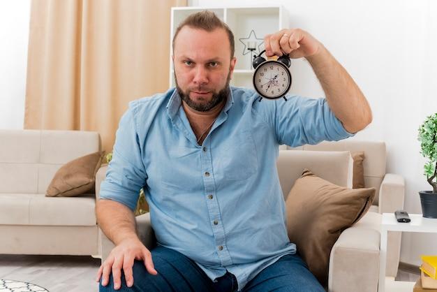 自信を持って大人のスラブ人がリビングルームの中で目覚まし時計を持って肘掛け椅子に座っています